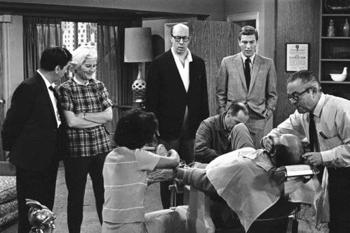 "FILE- In this April 11, 1963, file photo, standing from left, Morey Amsterdam, Rose Marie, and Richard Deacon, and Dick Van Dyke, right, gather around Carl Reiner, in barber chair during a rehearsal of an episode for the ""The Dick Van Dyke Show."" Family spokesman Harlan Boll said Marie, the wisecracking Sally Rogers of ""The Dick Van Dyke Show,� died Thursday, Dec. 28, 2017. She was 94. (AP Photo/David F. Smith, File)"