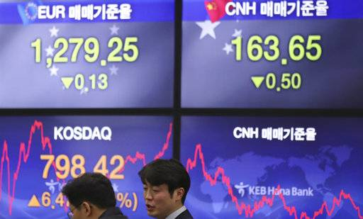 Currency traders talk near the screens showing the foreign exchange rates at the foreign exchange dealing room in Seoul, South Korea, Friday, Dec. 29, 2017. Asian stock markets mostly drifted higher on Friday after Wall Street finished with modest gains. (AP Photo/Lee Jin-man)
