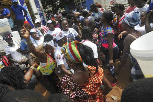 Supporters of former soccer player George Weah, Presidential candidate for the Coalition for Democratic Change, celebrate, in Monrovia, Liberia, Friday Dec. 29, 2017. The National Election Commission has declared George Weah president-elect and Jewel Howard-Taylor vice president-elect following the Dec. 26 runoff poll. (AP Photo/Abbas Dulleh)
