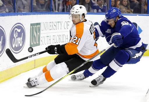 Philadelphia Flyers center Scott Laughton (21) flips the puck past Tampa Bay Lightning defenseman Andrej Sustr (62), of the Czech Republic, during the third period of an NHL hockey game Friday, Dec. 29, 2017, in Tampa, Fla. The Flyers won 5-3. (AP Photo/Chris O'Meara)