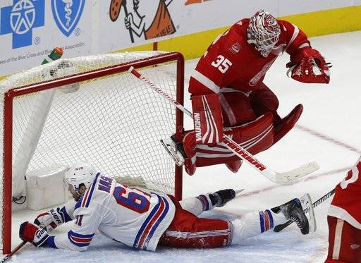 Detroit Red Wings goaltender Jimmy Howard (35) leaps to avoid New York Rangers right wing Rick Nash (61) who slides into the net during overtime of an NHL hockey game, Friday, Dec. 29, 2017, in Detroit. (AP Photo/Carlos Osorio)