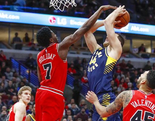 Chicago Bulls guard Justin Holiday (7) blocks Indiana Pacers forward Bojan Bogdanovic (44) during the first half of an NBA basketball game, Friday, Dec. 29, 2017, in Chicago.
