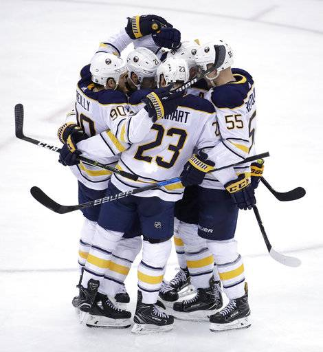 Buffalo Sabres players celebrate a goal by Jack Eichel (15) during the third period of an NHL hockey game against the New Jersey Devils, Friday, Dec. 29, 2017, in Newark, N.J. The Devils won 4-3 in overtime. (AP Photo/Julio Cortez)