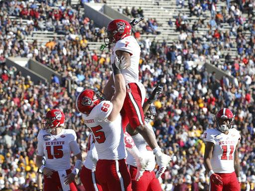 North Carolina State guard Garrett Bradbury hoists teammate Nyheim Hines following Hines' first-half touchdown against Arizona State in the Sun Bowl NCAA college football game in El Paso, Texas, Friday, Dec. 29, 2017. (Mark Lambie/The El Paso Times via AP)