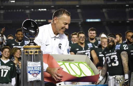 "Michigan State coach Mark Dantonio holds a cake with ""100"" written on it after Michigan State defeated Washington State 42-17 in the Holiday Bowl NCAA college football game Thursday, Dec. 28, 2017, in San Diego. It was Dantonio's 100th win to close his 11th season and his school-record fifth bowl. (AP Photo/Denis Poroy)"
