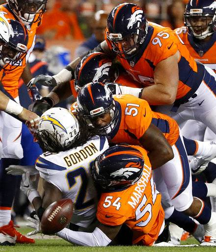 FILE - In this Sept. 11, 2017, file photo, Los Angeles Chargers running back Melvin Gordon (28) fumbles as Denver Broncos inside linebacker Brandon Marshall (54), inside linebacker Todd Davis (51) and defensive end Derek Wolfe (95) make the tackle during the first half of an NFL football game in Denver. Davis is growing accustomed to following fellow inside linebacker Brandon Marshall's lead. Like Marshall, Davis has excelled in Denver after getting cut multiple times by another NFL team. (AP Photo/Jack Dempsey, File)
