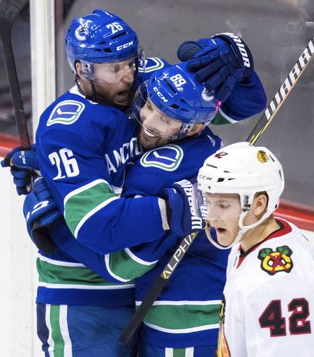 Vancouver Canucks' Thomas Vanek, left, of Austria, and Sam Gagner celebrate Vanek's goal as Chicago Blackhawks' Gustav Forsling, front right, of Sweden, skates past during the second period of an NHL hockey game Thursday, Dec. 28, 2017, in Vancouver, British Columbia. (Darryl Dyck/The Canadian Press via AP)