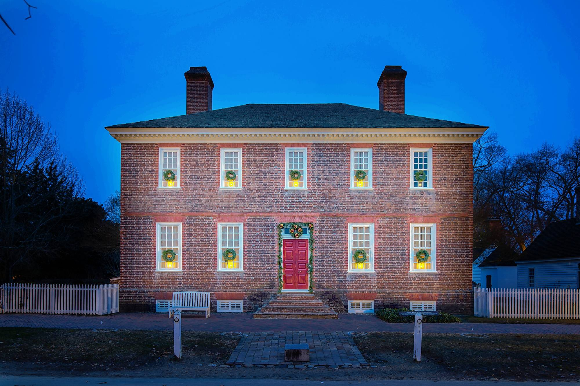 The George Wythe House, built in the mid-1750s, is decorated with greenery and fruit for the holidays and has a candle in every window. Wythe was Virginia's first signer of the Declaration of Independence.