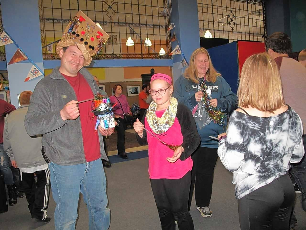 "Matt Jaeger of Crest Hill becomes a ""hat model"" just before noon Saturday as he celebrates New Year's Eve early with his friends Hannah Linko, 10, Heather Linko and Rebecca Linko, 10, at SciTech Hands On Museum in Aurora. The group was getting in place for a noon balloon drop to celebrate 2018."