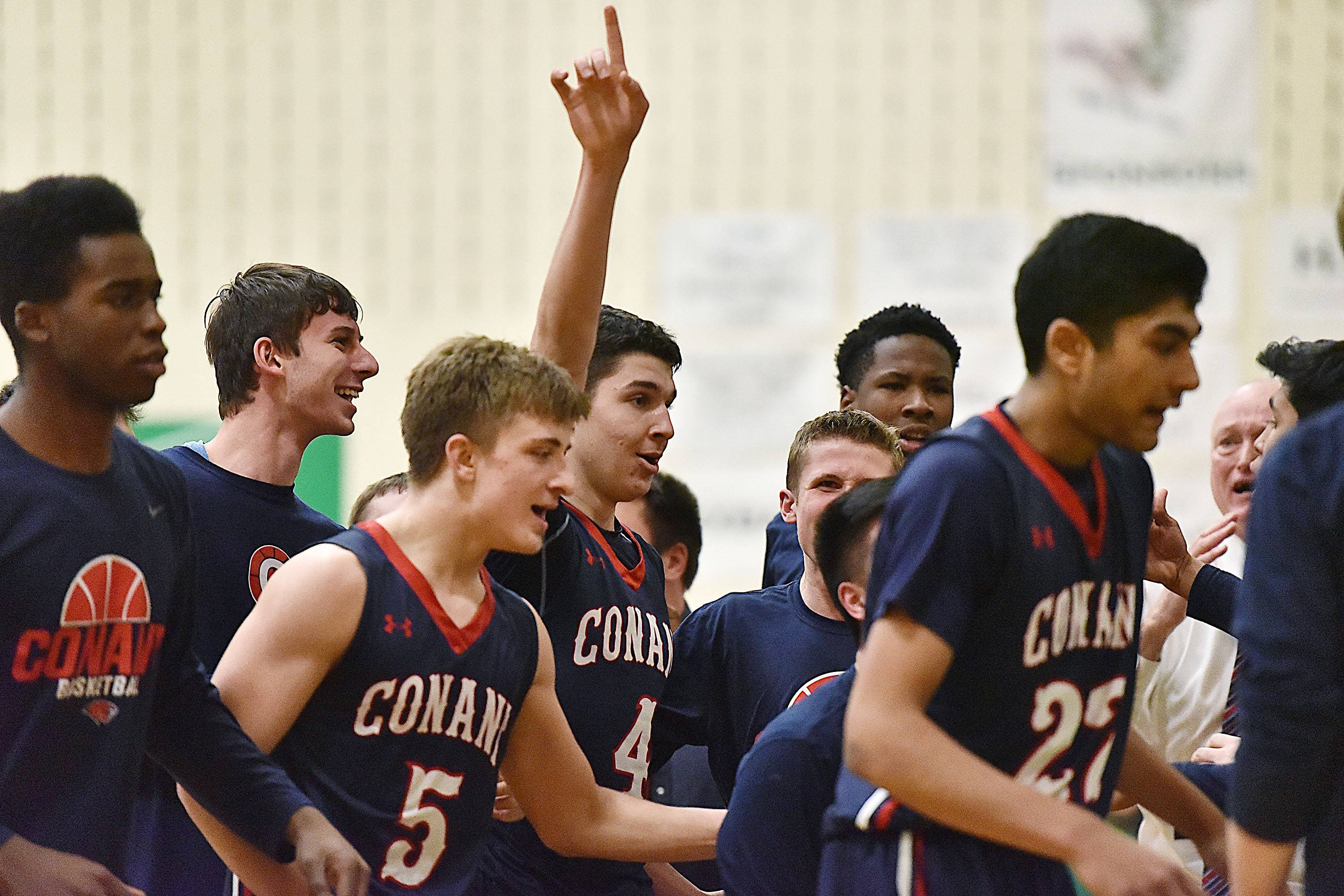 Conant's Jonathan Kolev signals who's No. 1 as he comes to the bench following his game-winning shot in double overtime against Brother Rice on Saturday in the Jack Tosh Holiday Classic championship game at York.