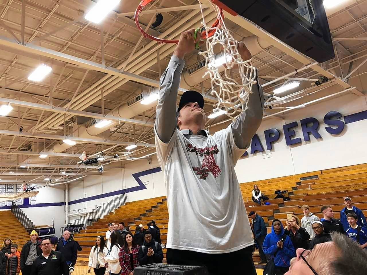Burlington Central boys basketball coach Brett Porto cuts down the net after the Rockets won the Plano Christmas Classic championship, 44-39 in overtime against Peoria Notre Dame Saturday night.