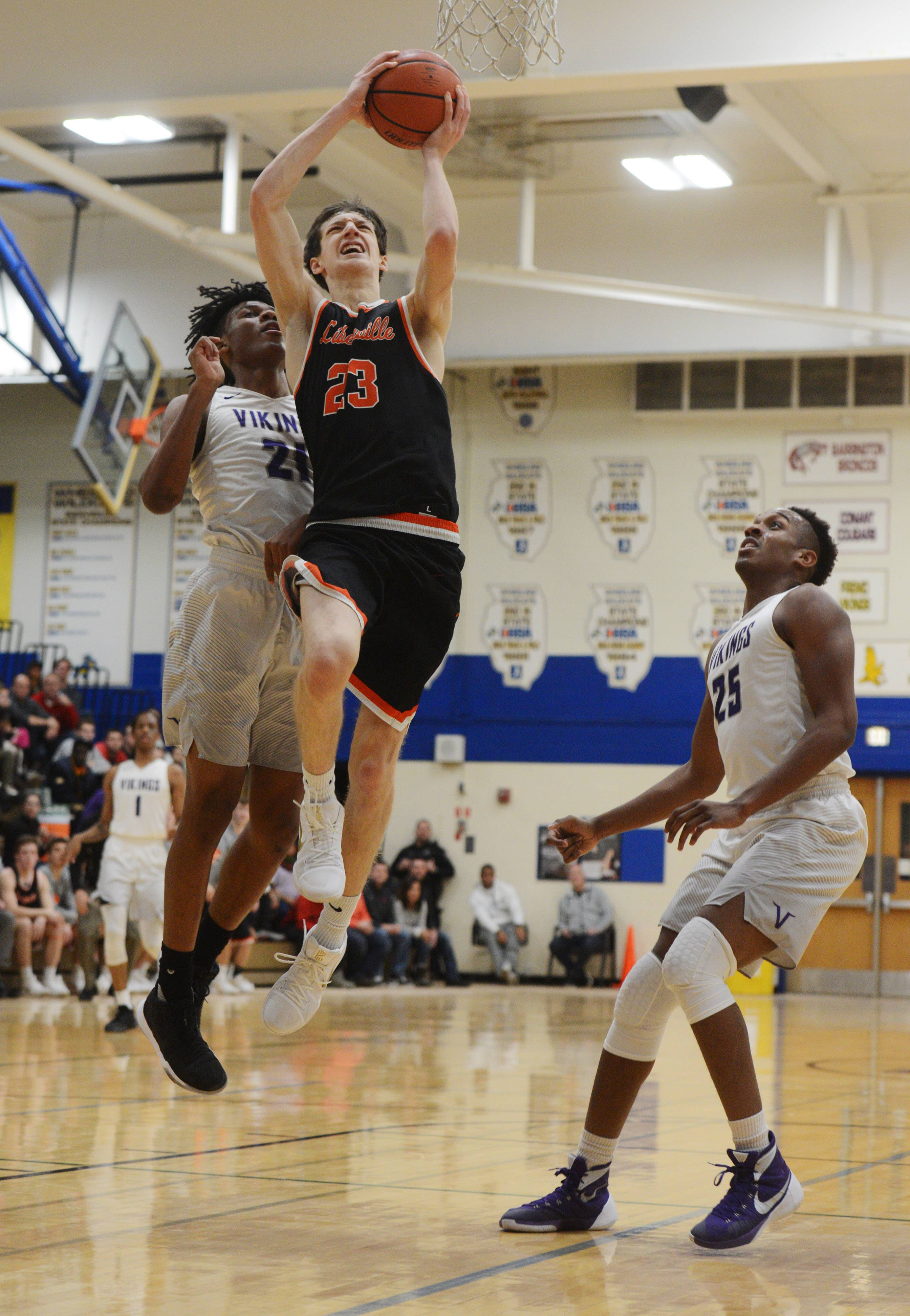 Libertyville's Drew Peterson shoots against the defense of Niles North's Jailen Butler, left, and Lamar Nicholson Jr. during the championship game of the Wheeling Hardwood Classic on Saturday.