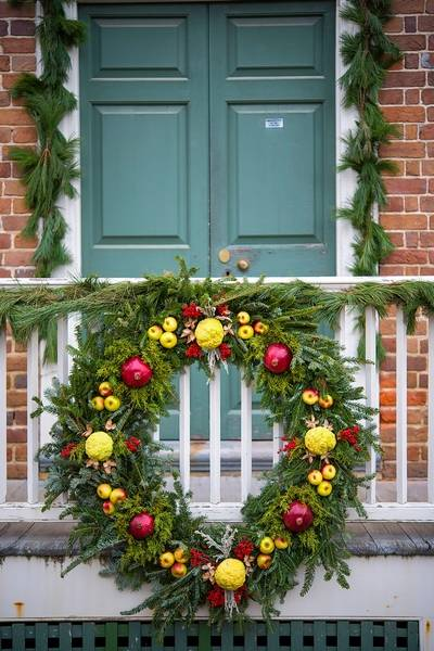 a large della robbia style wreath in front of the roscow cole house in colonial