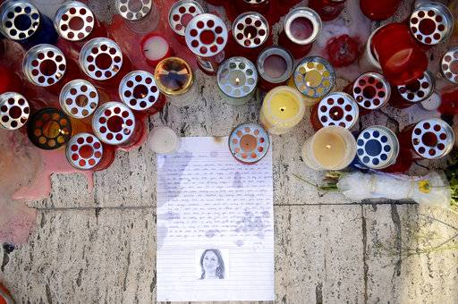 FILE - A Tuesday Oct. 17, 2017 file photo showing candles, notes and paper cuttings next to the Love Monument in St. Julian, Malta, the day after the killing of journalist Daphne Caruana Galizia. At least 81 reporters were killed doing their jobs this year, while violence and harassment against media staff has skyrocketed, the world's biggest journalists' organization says. (AP Photo/Rene Rossignaud, File)