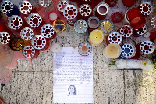 FILE - A Tuesday Oct. 17, 2017 file photo showing candles, notes and paper cuttings next to the Love Monument in St. Julian, Malta,  the day after the killing of journalist Daphne Caruana Galizia. At least 81 reporters were killed doing their jobs this year, while violence and harassment against media staff has skyrocketed, the world's biggest journalists' organization says.