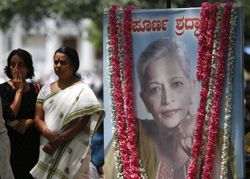 FILE - A Wednesday, Sept. 6, 2017 file photo showing mourners standing next to a portrait of Indian journalist Gauri Lankesh during the public viewing of her body in Bangalore, India. The International Federation of Journalists also expressed concern about India, the world's largest democracy, where it said that attacks on journalists are being motivated by violent populism.