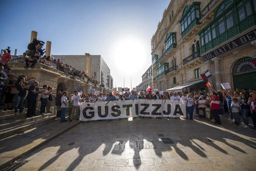 "FILE - A  Sunday, Oct. 22, 2017 file photo showing a banner reading ""justice"" displayed at the start of a rally in Malta to honor an anti-corruption reporter Daphne Caruana Galizia, killed by a car bomb on Oct. 16, in the capital city of Malta, Valletta. At least 81 reporters were killed doing their jobs this year, while violence and harassment against media staff has skyrocketed, the world's biggest journalists' organization says."
