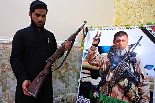 In this Tuesday, Dec. 5, 2017 photo, Talib, the son of Iraqi sniper Ali Jayad al-Salhi, 65, a volunteer with Popular Mobilization Forces killed fighting Islamic State militants, poses with a weapon next to his father's poster in his home in Basra, Iraq. Al-Salhi, an expert sniper and veteran of multiple wars, was vaulted into legend. Shiites around Iraq trade stories of how, out of piety, he left his home, wife, 10 children and 20 grandchildren to join a Shiite militia to fight in what he saw as a war between humanity and evil. (AP Photo/Nabil al-Jurani)