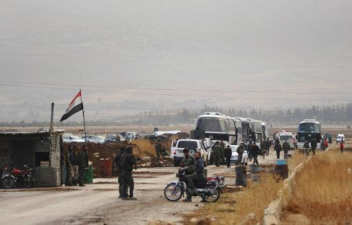 In this photo released on Friday, Dec. 29, 2017 by the Syrian official news agency SANA, Syrian government forces stand on their checkpoint as busses, background, wait to evacuate Syrian militants and their families from Beit Jin village, in the southern province of Daraa, Syria. Dozens of Syrian militants and their families have left aboard buses an area where they have been besieged by government forces near the Israeli-occupied Golan Heights part of a deal to clear yet another district from insurgents. (SANA via AP)