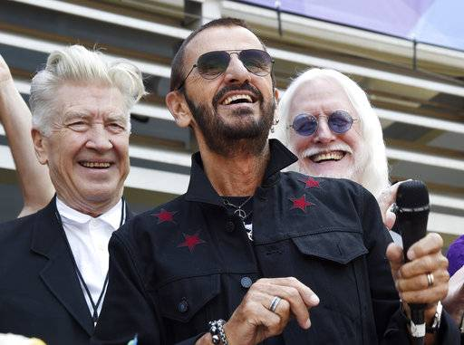 "FILE - In this Friday, July 7, 2017 file photo, Ringo Starr, center, is joined by guests including filmmaker David Lynch, left, and musician Edgar Winter, second from right, during a 77th birthday celebration for Starr outside Capitol Records, in Los Angeles. A Beatle and a Bee Gee have topped the list of celebrated people designated to receive knighthoods and other awards in the New Year's Honors List. They are joined by a noted children's author celebrated for ""War Horse,� a politician who fought in vain to keep Britain in the European Union, and many others, including renowned researchers, volunteers and actors. (Photo by Chris Pizzello/Invision/AP, File)"