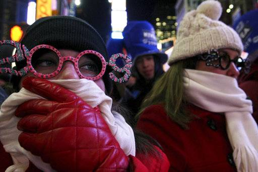 FILE- In this Dec. 31, 2008 file photo, Allison Smith of Jacksonville, Fla, left, tries to keep warm as she and others take part in the New Year's Eve festivities in New York's Times Square. Brutal weather has iced plans for scores of events in the Northeast U.S. from New Year's Eve through New Year's Day, but not in New York City, where people will start gathering in Times Square up to nine hours before the famous ball drop. (AP Photo/Tina Fineberg, File)