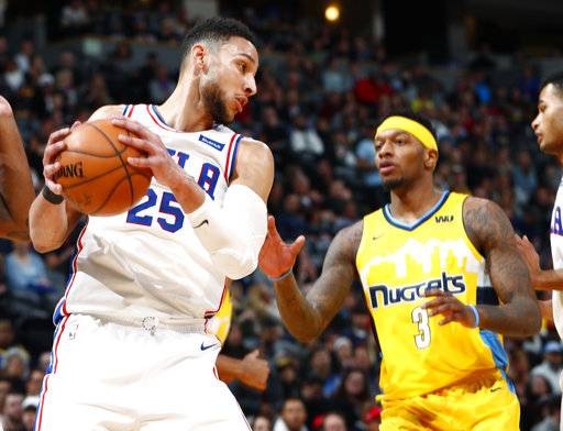 Philadelphia 76ers guard Ben Simmons, left, pulls in a rebound in front of Denver Nuggets guard Torrey Craig in the first half of an NBA basketball game Saturday, Dec. 30, 2017, in Denver. (AP Photo/David Zalubowski)