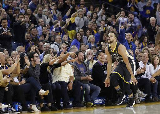 Golden State Warriors guard Stephen Curry celebrates in front of fans after scoring against the Memphis Grizzlies during the first half of an NBA basketball game in Oakland, Calif., Saturday, Dec. 30, 2017. (AP Photo/Jeff Chiu)