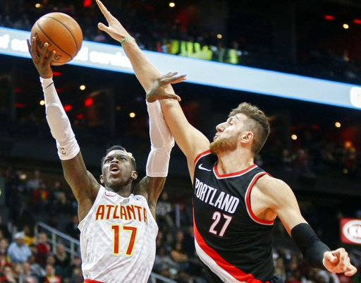 Atlanta Hawks guard Dennis Schroder (17) shoots the ball past Portland Trail Blazers center Jusuf Nurkic (27) in the second half of an NBA basketball game, Saturday, Dec. 30, 2017, in Atlanta. The Hawks won 104-89. (AP Photo/Brett Davis)