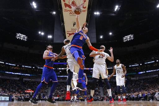 New York Knicks forward Kristaps Porzingis (6) dunks over New Orleans Pelicans forward Anthony Davis (23) and center DeMarcus Cousins (0) during the second half of an NBA basketball game in New Orleans, Saturday, Dec. 30, 2017. The Knicks won 105-103. (AP Photo/Jonathan Bachman)