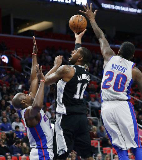 San Antonio Spurs forward LaMarcus Aldridge (12) shoots over Detroit Pistons forward Anthony Tolliver (43) and guard Dwight Buycks (20) during the first half of an NBA basketball game, Saturday, Dec. 30, 2017, in Detroit. (AP Photo/Carlos Osorio)