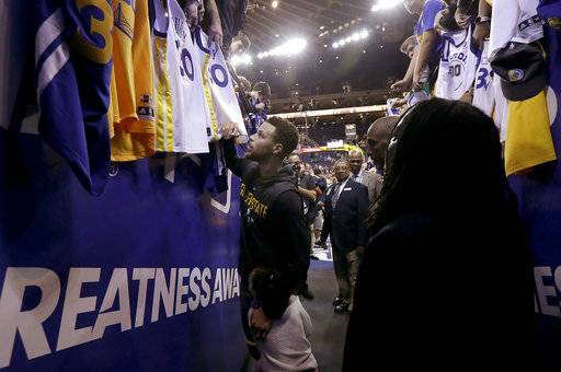 Golden State Warriors guard Stephen Curry holds on to his daughter Riley while signing autographs for fans before the team's NBA basketball game against the Memphis Grizzlies in Oakland, Calif., Saturday, Dec. 30, 2017. Curry is returning to the court Saturday night after missing 11 games with a sprained right ankle. (AP Photo/Jeff Chiu)