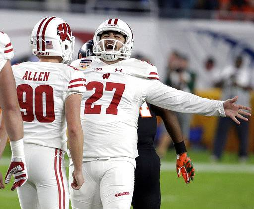Wisconsin place kicker Rafael Gaglianone (27) reacts to a 47-yard field goal, during the second half of the Orange Bowl NCAA college football game against Miami, Saturday, Dec. 30, 2017, in Miami Gardens, Fla. To the left is punter Connor Allen (90). (AP Photo/Lynne Sladky)