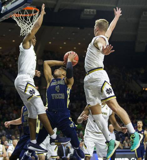 Georgia Tech's Brandon Alston, center, goes up for a shot as Notre Dame's D.J. Harvey, left, and Rex Pflueger, right, defend during the first half of an NCAA college basketball game Saturday, Dec. 30, 2017, in South Bend, Ind. (AP Photo/Robert Franklin)