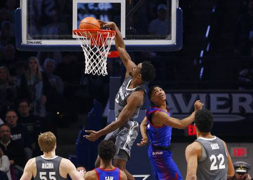 Xavier guard Quentin Goodin, center, dunks against DePaul guard Justin Roberts during the second half of an NCAA college basketball game, Saturday Dec. 30, 2017, in Cincinnati. (AP Photo/Gary Landers)