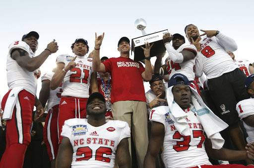 North Carolina State celebrates with the Hyundai Sun Bowl trophy after defeating Arizona State 52-31 in the NCAA college football game Friday, Dec. 29, 2017, in El Paso, Texas. (Mark Lambie/The El Paso Times via AP)