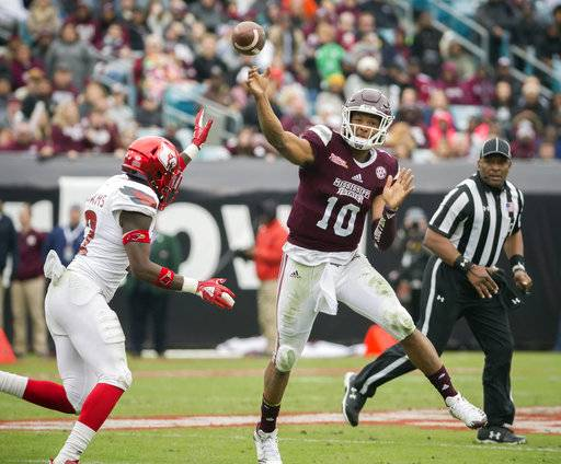 Mississippi State quarterback Keytaon Thompson (10) throws a pass while being chased by Louisville safety Chucky Williams (22) during the first half of the TaxSlayer Bowl NCAA college football game, Saturday, Dec. 30, 2017, in Jacksonville, Fla. (AP Photo/Stephen B. Morton)