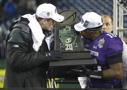 Northwestern quarterback Clayton Thorson, left, and safety Godwin Igwebuike (16) kiss the trophy after Northwestern beat Kentucky 24-23 in the Music City Bowl NCAA college football game Friday, Dec. 29, 2017, in Nashville, Tenn. Thorson was injured during the game. (AP Photo/Mark Humphrey)