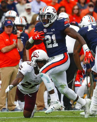 "FILE - This Nov. 18, 2017, file photo shows Auburn running back Kerryon Johnson (21) carrying the ball for a first down as Louisiana Monroe cornerback Corey Straughter (21) tries to tackle him during the first half of an NCAA college football game in Auburn, Ala. The biggest key to Auburn's offensive success, running back Kerryon Johnson, says he's ""running like my old self� and eager to play in the Peach Bowl against Central Florida on Monday, Jan. 1, 2018. (AP Photo/Butch Dill, File )"