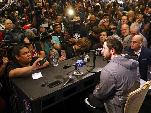 Oklahoma quarterback Baker Mayfield, battling a flu-like illness, makes his first media appearance showing up late for the last 20 minutes of his team's Media Day Saturday, Dec. 30, 2017, for the Rose Bowl Game in Los Angeles. (Curtis Compton/Atlanta Journal-Constitution via AP)