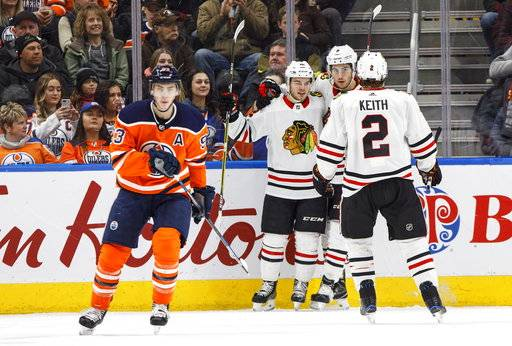 Chicago Blackhawks' Alex DeBrincat (12), Nick Schmaltz (8) and Duncan Keith (2) celebrate a goal as Edmonton Oilers' Ryan Nugent-Hopkins (93) skates past during the second period of an NHL hockey game Friday, Dec. 29, 2017, in Edmonton, Alberta. (Jason Franson/The Canadian Press via AP)