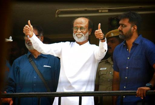 Indian movie superstar Rajinikanth, center, gives thumbs up sign to his fans after announcement to launch his own political party, in Chennai, India, Sunday, Dec. 31, 2017. Rajinikanth is entering politics in his southern Indian state with a plan to launch his own party, calling it his duty. The 67-year-old told his cheering supporters that his objective is to change the system and bring good governance to Tamil Nadu.
