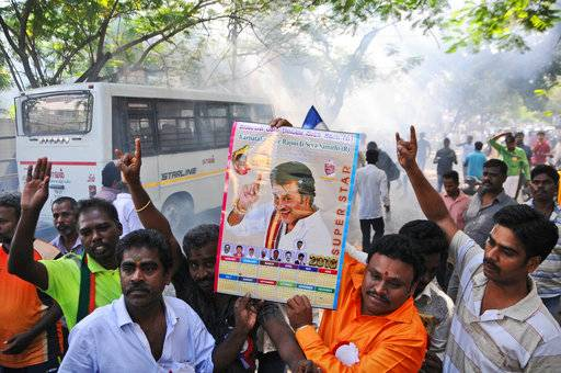 Indian movie superstar Rajinikanth fans burn firecrackers and hold his photograph after his announcement to launch his own political party, in Chennai, India, Sunday, Dec.31, 2017. Rajinikanth is entering politics in his southern Indian state with a plan to launch his own party, calling it his duty. The 67-year-old told his cheering supporters that his objective is to change the system and bring good governance to Tamil Nadu.
