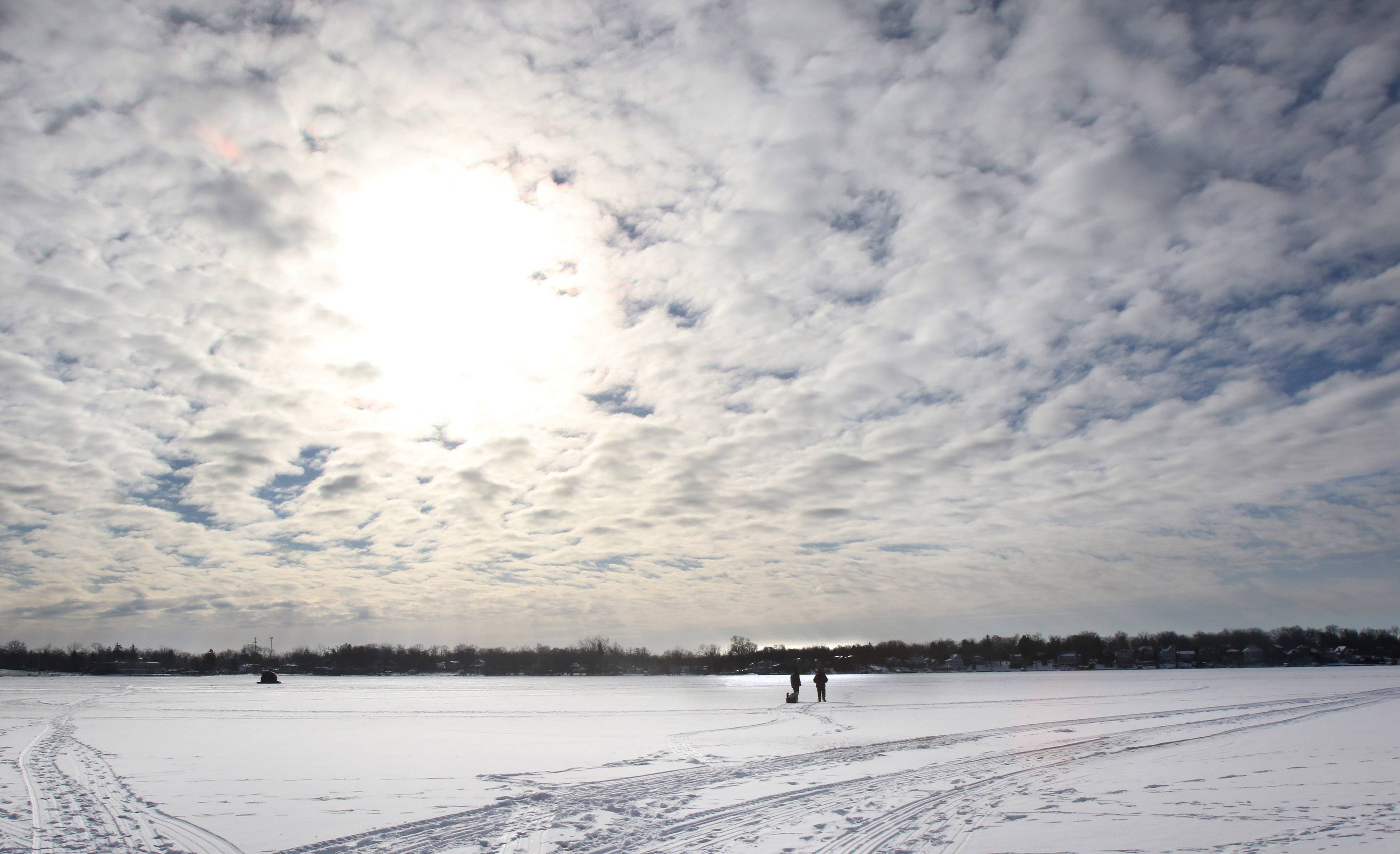 Andrius Janiukstys, left, and his father, Daugyidas of Mundelein, walk on the frozen ice on Diamond Lake in Mundelein as they go ice fishing Sunday. Extremely cold temperatures are expected throughout the week.