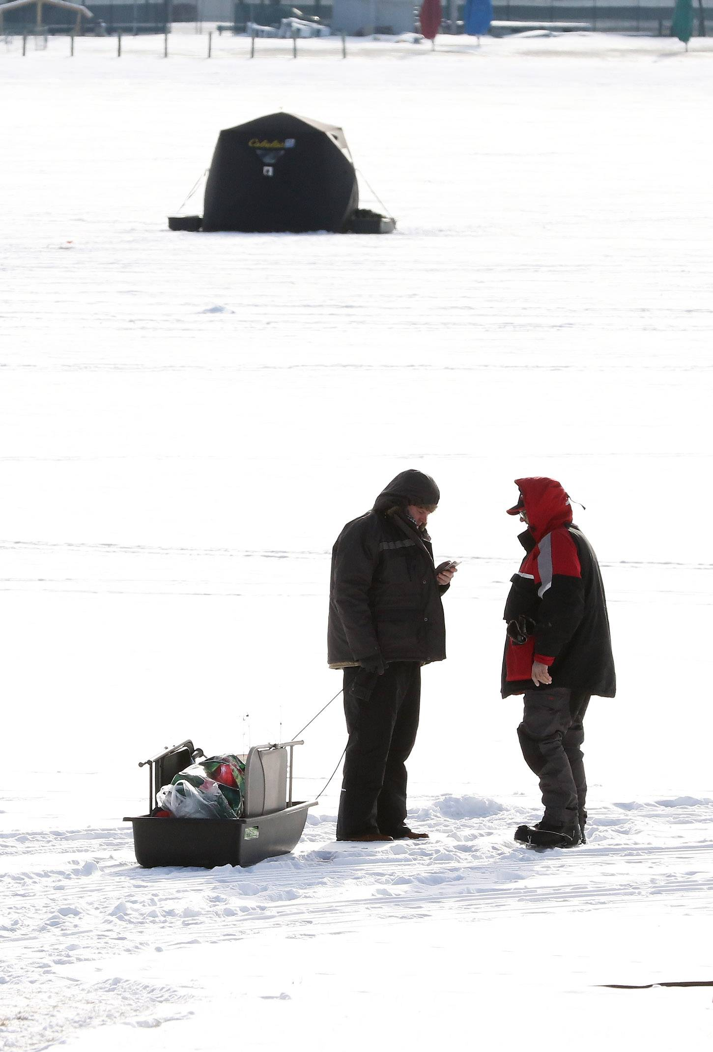 Andrius Janiukstys, left, and his father, Daugyidas of Mundelein, walk of the frozen ice on Diamond Lake in Mundelein as they go ice fishing Sunday. Temperatures are expected to be bitterly cold throughout the week.