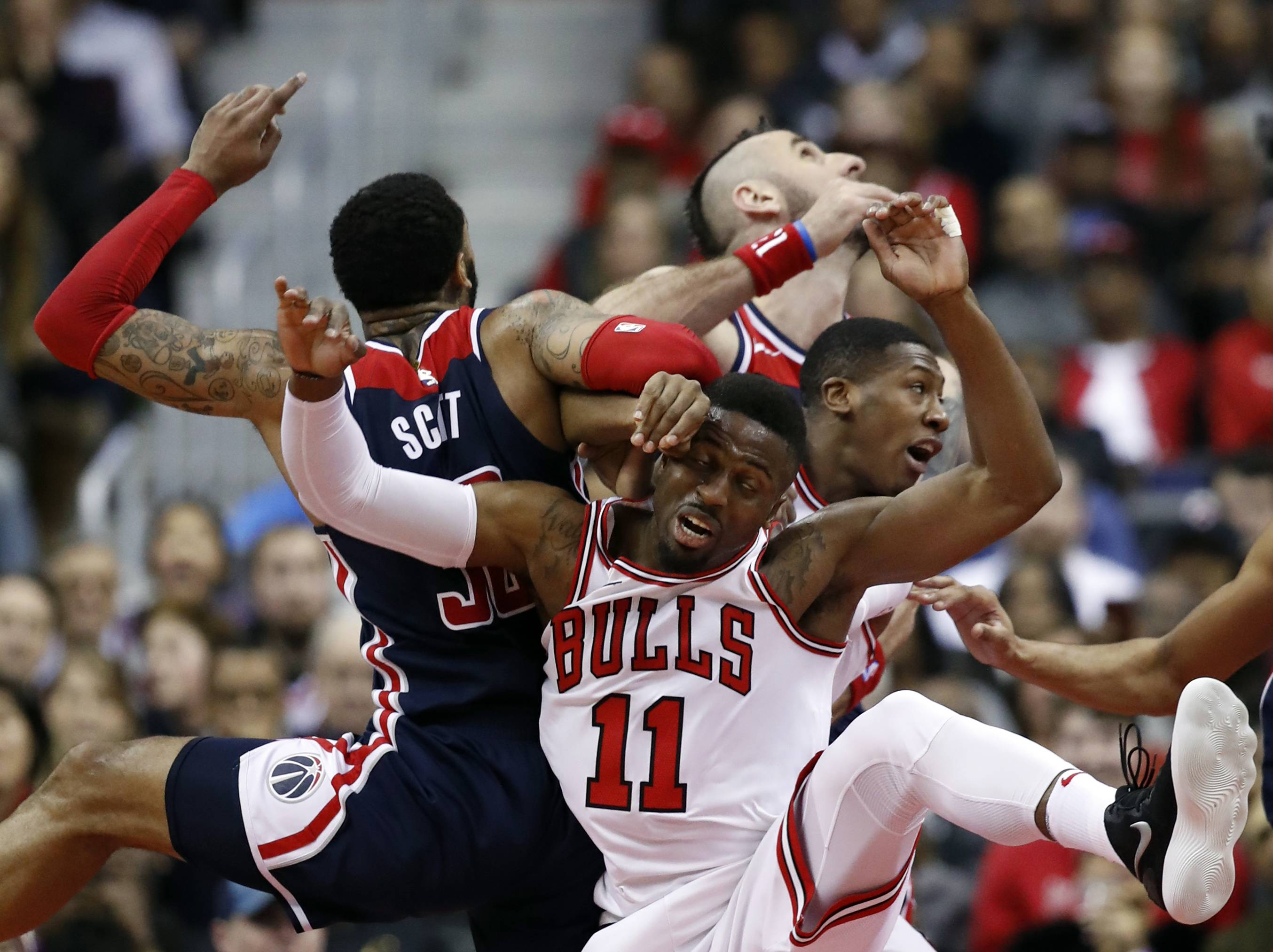 Washington Wizards forward Mike Scott, left, Chicago Bulls guard David Nwaba, Washington Wizards center Marcin Gortat, from Poland, and Chicago Bulls guard Kris Dunn get tangled up as they go for a rebound during the second half of an NBA basketball game, Sunday, Dec. 31, 2017, in Washington. The Wizards won 114-110.