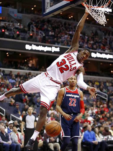 Chicago Bulls guard Kris Dunn (32) hangs from the rim after dunking in front of Washington Wizards forward Otto Porter Jr. (22) during the first half of an NBA basketball game Sunday, Dec. 31, 2017, in Washington.