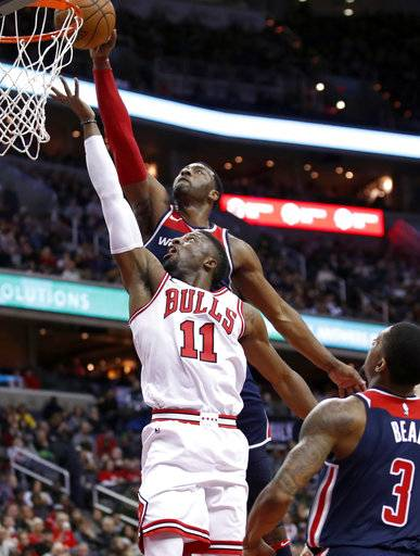 Washington Wizards guard John Wall, top, blocks a shot by Chicago Bulls guard David Nwaba (11) during the first half of an NBA basketball game Sunday, Dec. 31, 2017, in Washington.