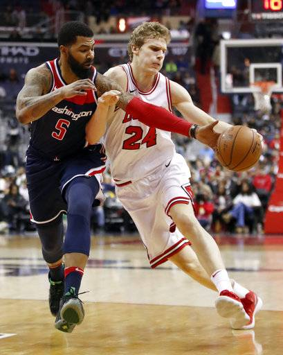 Washington Wizards forward Markieff Morris (5) knocks the ball away from Chicago Bulls forward Lauri Markkanen (24), from Finland, during the first half of an NBA basketball game Sunday, Dec. 31, 2017, in Washington.
