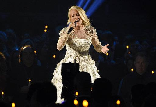 "FILE - In this Nov. 8, 2017, file photo, Carrie Underwood performs ""Softly and Tenderly"" during an In Memoriam tribute at the 51st annual CMA Awards at the Bridgestone Arena in Nashville, Tenn. Country singer Underwood is bringing in 2018 by sharing more details about more injuries that she suffered after a fall that broke her wrist. In a blog post to fans on New Year's Day, Underwood says she sustained a facial injury that required 40-50 stitches and that she's ""not quite looking the same."" (Photo by Chris Pizzello/Invision/AP, File)"