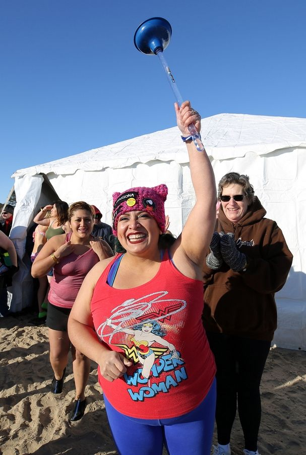 Joann Flores of Waukegan triumphantly raises her plunger. She has participated in all 19 Polar Plunges at the Waukegan beach.